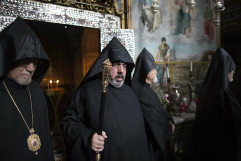 Archbishop Nourhan Manougian (C), 65, the new elected Armenian patriarch of Jerusalem, walks at the Armenian Church in Jerusalem's old city on January 24 2013. AFP PHOTO/MENAHEM KAHANA