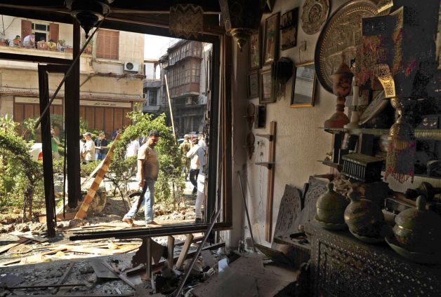 This photo released by the Syrian official news agency SANA, shows a Syrian security agent looking at a damaged antique shop after a blast struck in the vicinity of the Greek Orthodox Virgin Mary Church in the predominantly Christian neighborhood of Bab Sharqi in central Damascus, Syria, Thursday, June 27, 2013. A suicide attacker blew himself up near one of the main churches in the Syrian capital Thursday, killing several people, state-run TV said. Photo: SANA