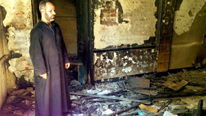A priest stands inside his destroyed church