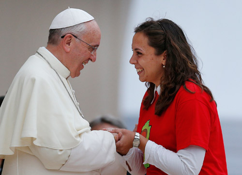 Pope Francis greets a young woman during an encounter with youth in the piazza outside the Basilica of St. Mary of the Angels in Assisi, Italy, Oct. 4. (CNS/Paul Haring)