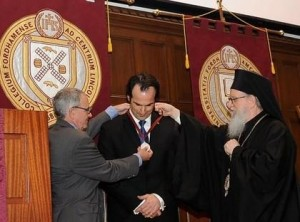 Fordham Provost Stephen Freedman, along with Archbishop Demetrios, present Professor Aristotle Papanikolaou with a ceremonial medal commemorating his installation.