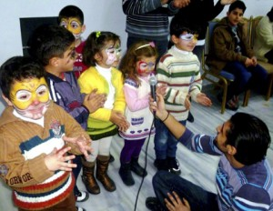 Face painting, singing and performing are all activities used by IOCC/GOPA trauma counselors to help displaced Syrian children express their feelings through art and play. These children are among 2,300 displaced Syrian men, women and children who have benefited from the counseling program since it was first provided in March 2012. Photo: Jennifer Romanos/IOCC