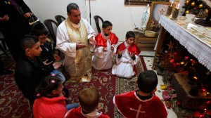 Father Raymond Moussalli, a Syrian priest, prays with Iraqi children for peace in Iraq and Syria during a Mass at a Chaldean Catholic church in Amman, Jordan, last December. CNS photo from Reuters
