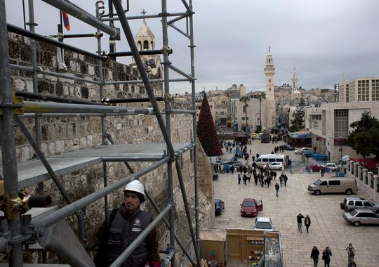 In this Tuesday Dec. 10, 2013, photograph, tourists walk around the Church of the Nativity in the West Bank city of Bethlehem. Wrapped in scaffolding, the basilica is having a much-needed facelift after 600 years.(Photo: Nasser Nasser, AP)