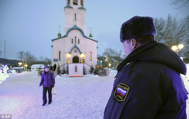 Shooting: A policeman watches as a churchgoer leaves the Russian Orthodox cathedral in Yuzhno-Sakhalinsk, where a gunman opened fire on Sunday