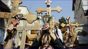 Orthodox Christian worshippers hold crosses as they take part in the Eastern and Orthodox Church's Good Friday procession along the Via Dolorosa in Jerusalem's Old City (photo: Reuters).