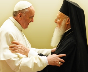 Pope Francis and Patriarch Bartholomew fraternally embrace one another.