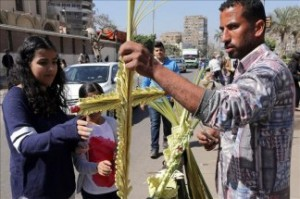 An Egyptian Coptic Christian vendor offers a cross made of weaved palms leaves on Palm Sunday at Heliopolis in Cairo, Egypt, 05 April 2015. EFE/EPA/KHALED ELFIQI